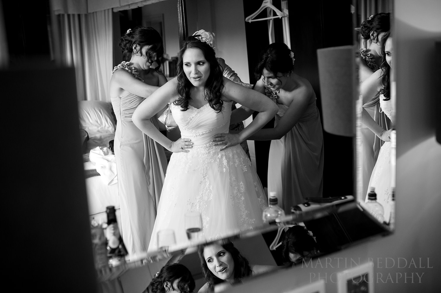 Bride getting into her wedding dress reflected in the mirror