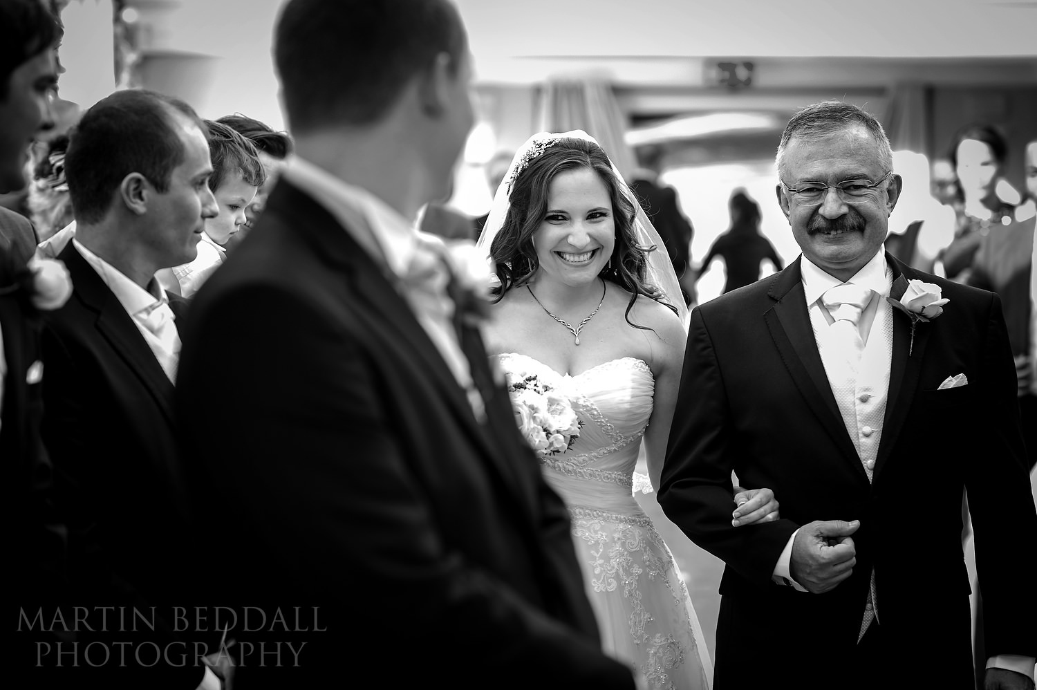 Groom looks back to bride in the aisle