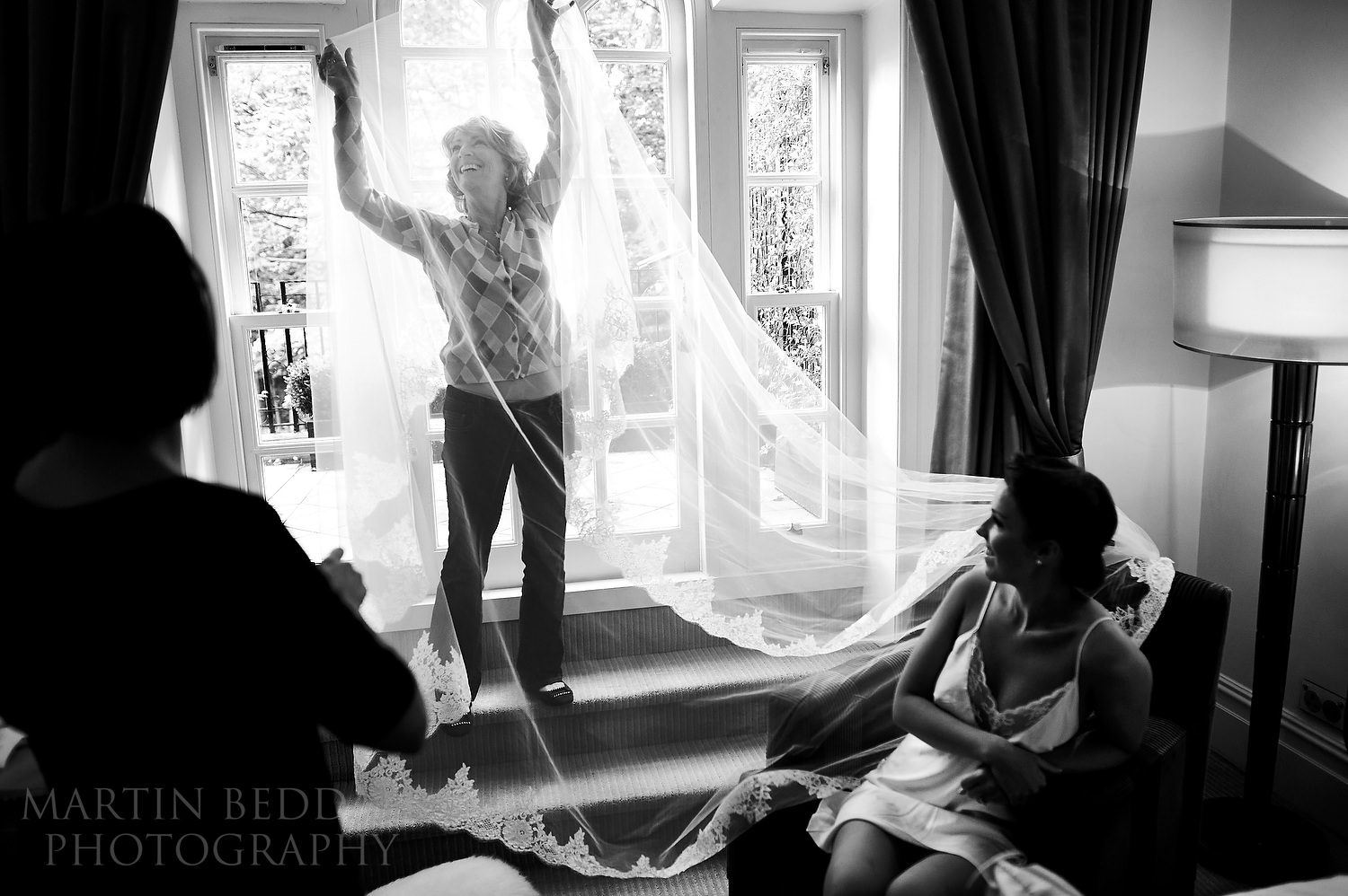 Bride's mother plays with her wedding veil