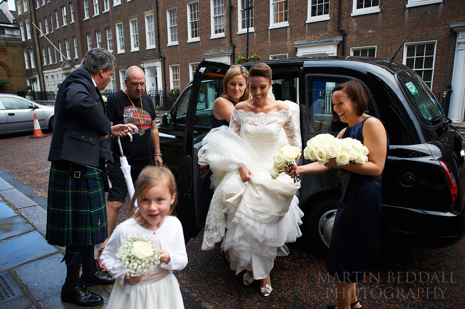 Bride arrives at St Etheldreda's church in a black taxi cab
