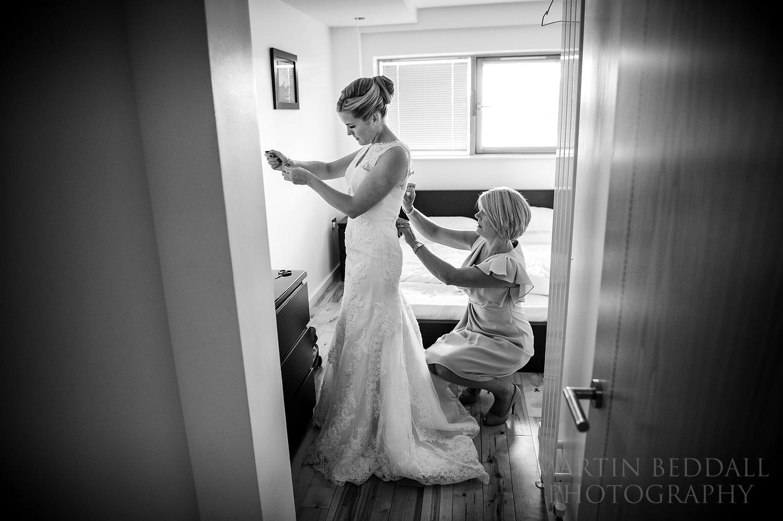 Bride's mother helping get into her wedding dress