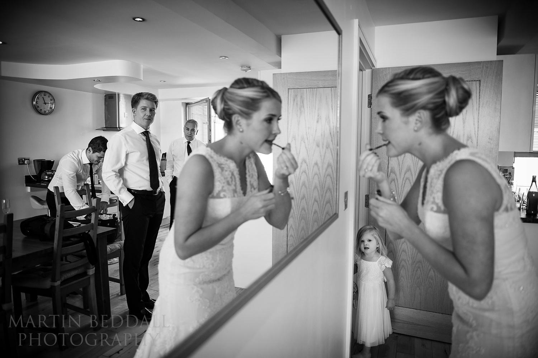 Flowergirl watches bride do her lipstick