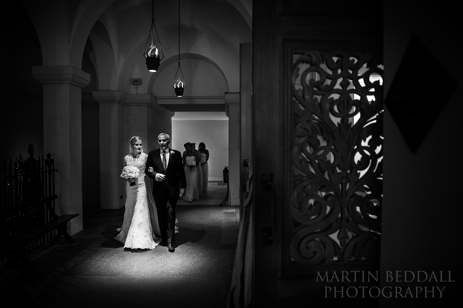 Bride escorted by her father to the OBE Chapel