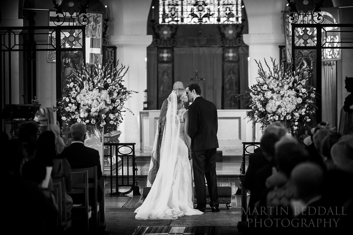 Bride and groom kiss in the OBE Chapel