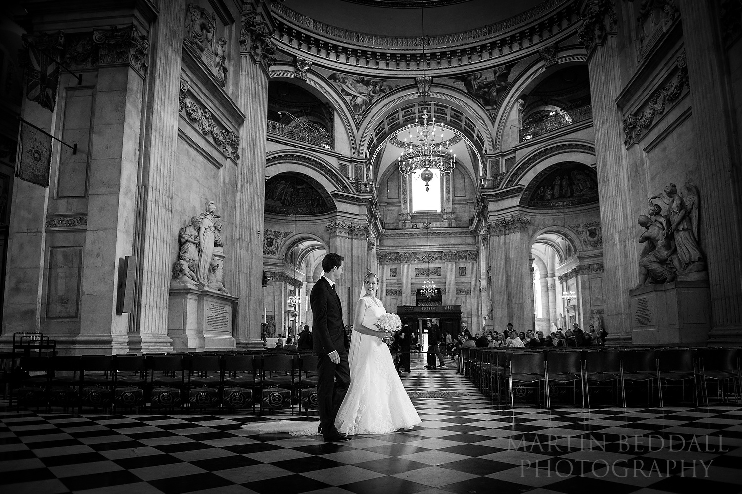 Bride and groom walk through St Paul's Cathedral