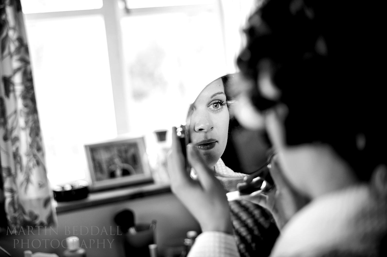 Bride applies her makeup