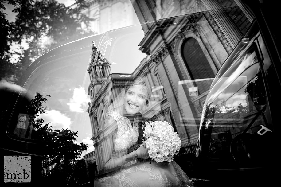Award winning wedding photography of bride reflected through the car window as she arrives at St Pauls