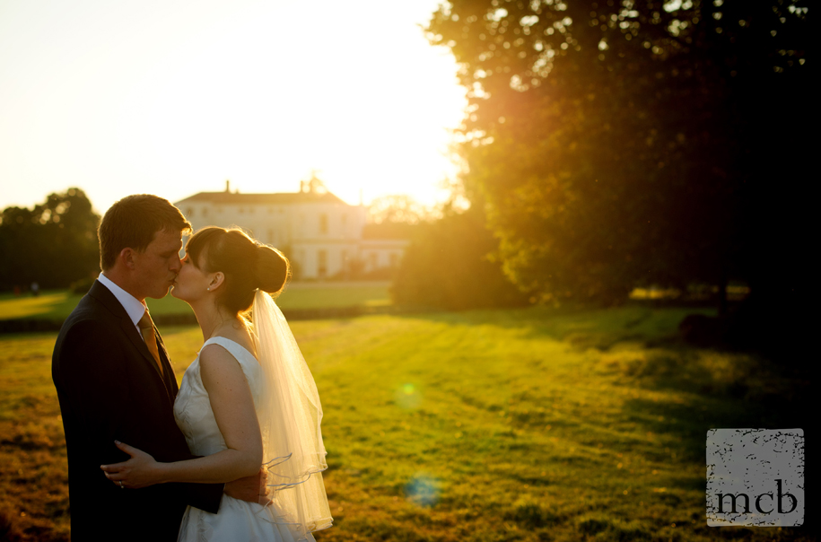 Bride and groom kiss in the sunset at Newick Park