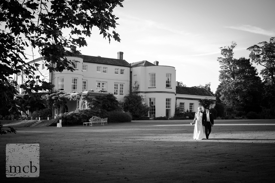 Bride and groom walk hand in hand in the evening sunlight