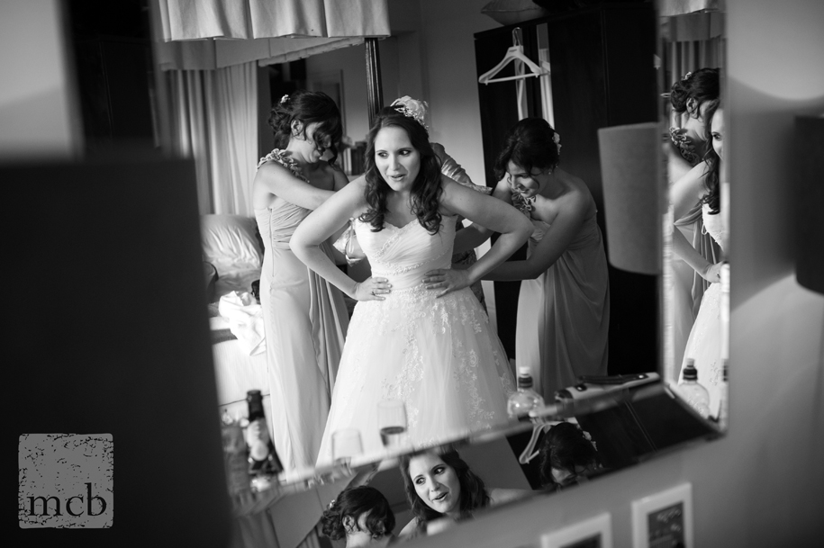 Bride reflected in mirror as she gets in her dress