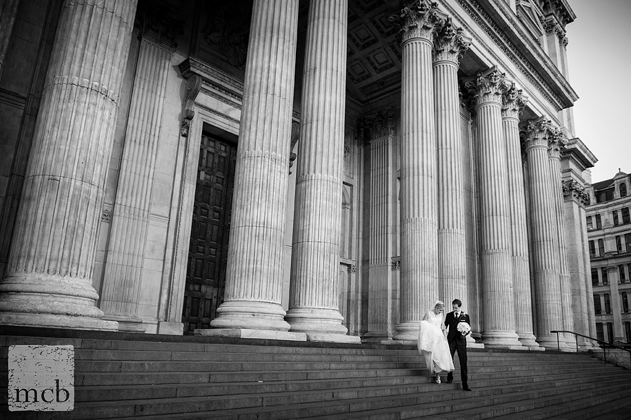 A quiet moment for the bride and groom on the steps of St Paul's Cathedral