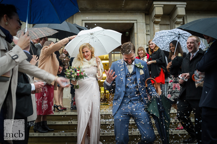 Bride and groom are showered in confetti as they leave Hackney Town Hall