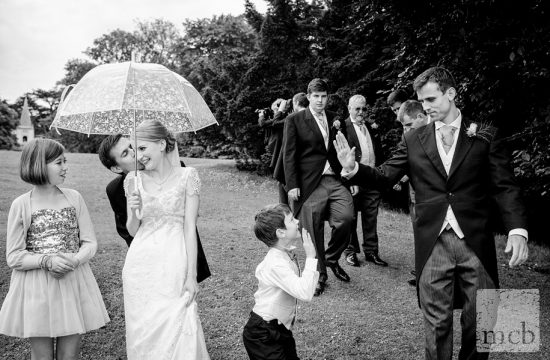 Bride and groom kiss under an umbrella