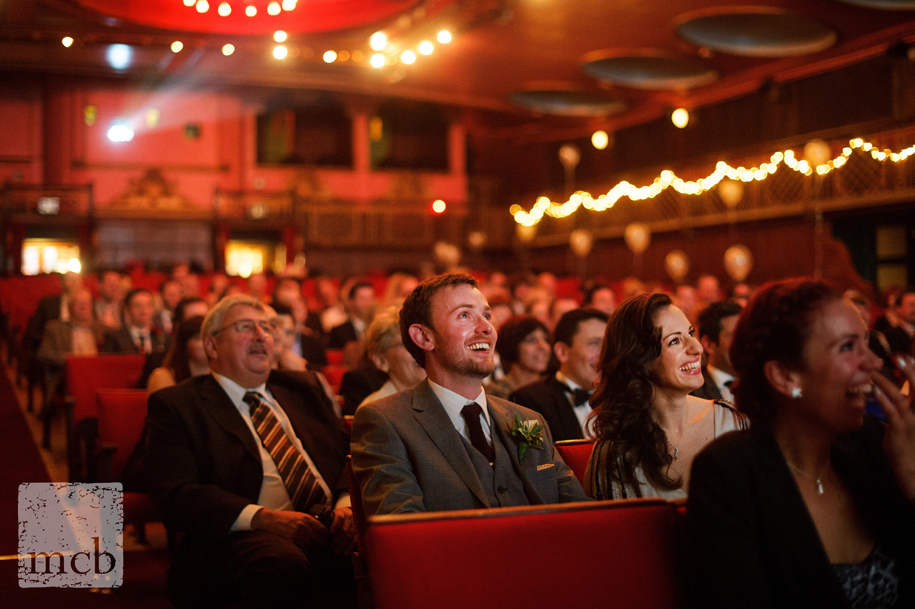 Couple watch their film at a wedding in a cinema
