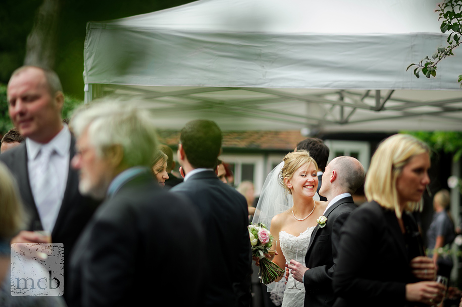 Bride smiling at the groom amongst the crowded reception