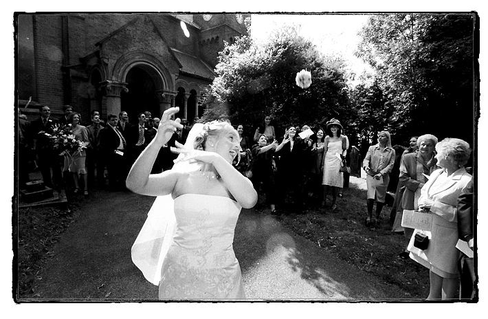 Bride throws her wedding bouquet towards the guests