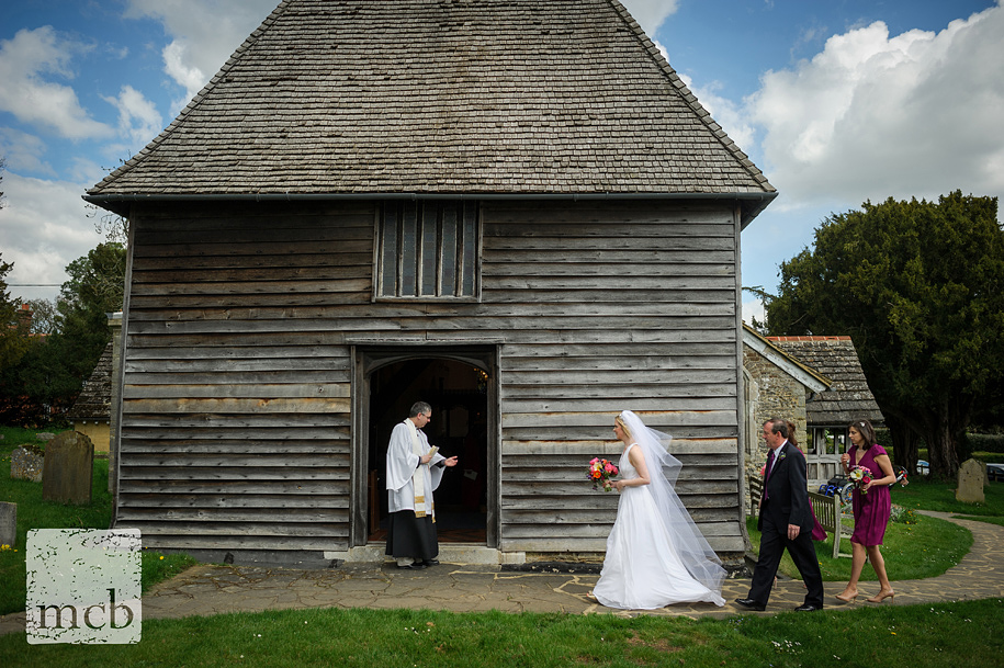 Bride walks to the entrance of St Peters church in Newdigate