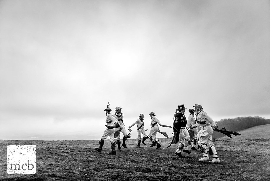Morris dancers atop Chanctonbury Hill on May day at sunrise