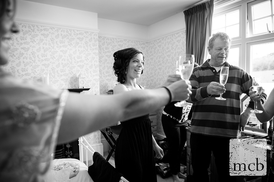 Bride shares a galss of champagne with family and friends