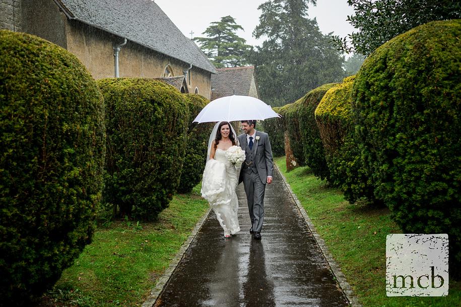 Bride and groom walk through the heavy rain