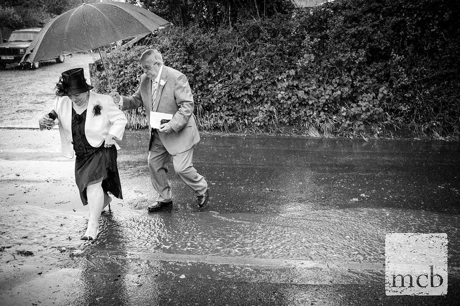 wet wedding guests cross a stream