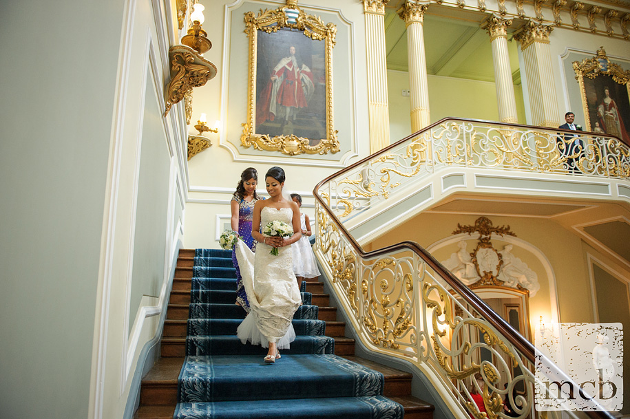 Bride walks down the main staircase at Wrest Park