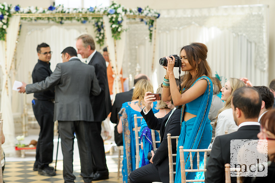 Glamourous wedding guest taking photos