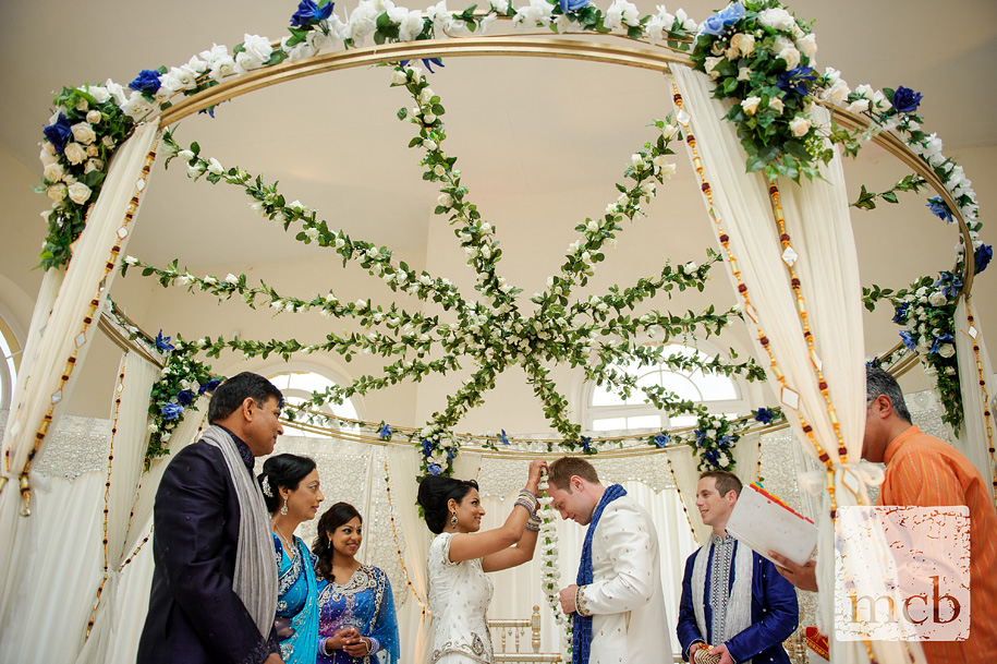 Bride places garland of flowers around the groom's neck