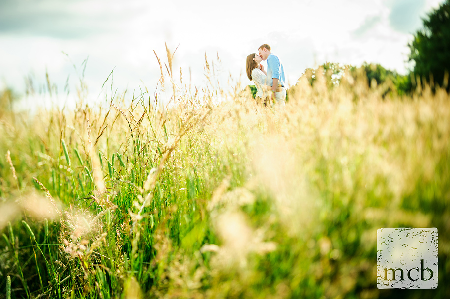 Couple kissing shoot low in the grass on Hampstead Heath