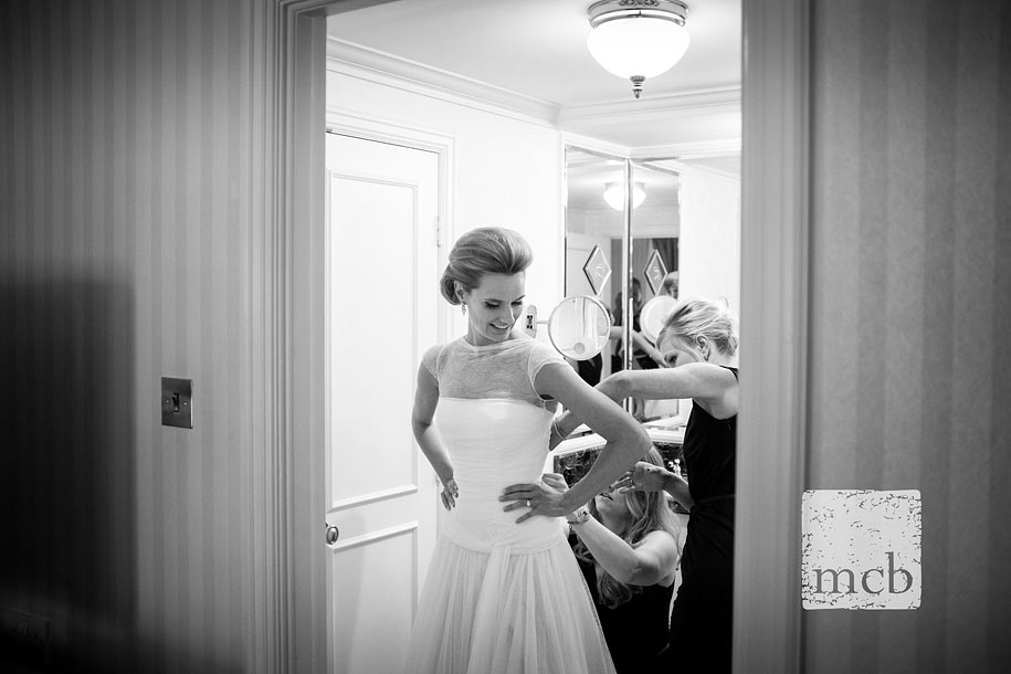 Bridesmaids help the bride into her dress in the bathroom