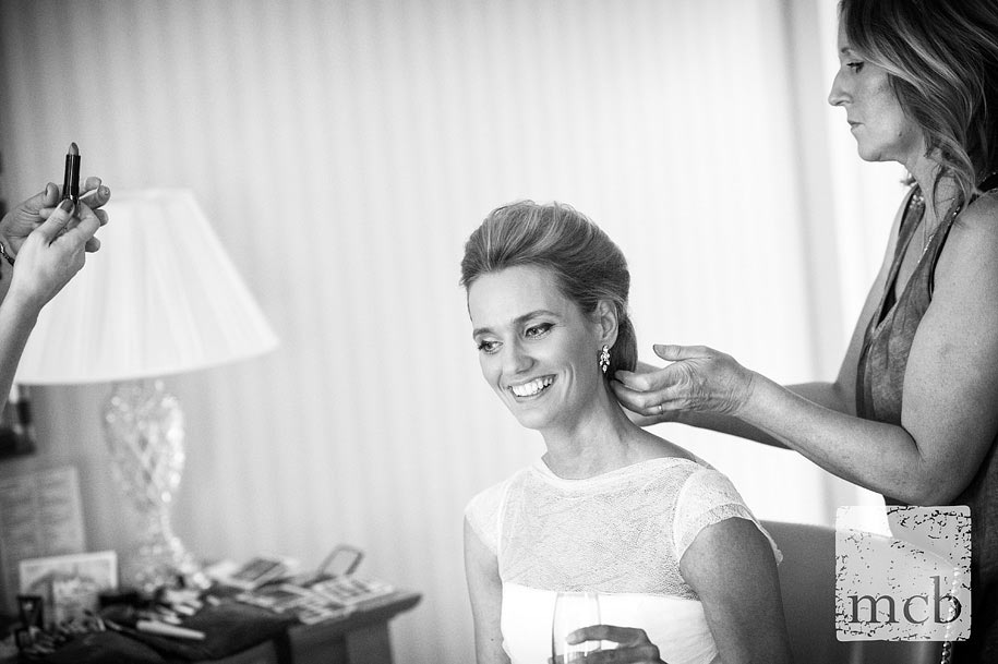 Smiling bride has her hair adjusted