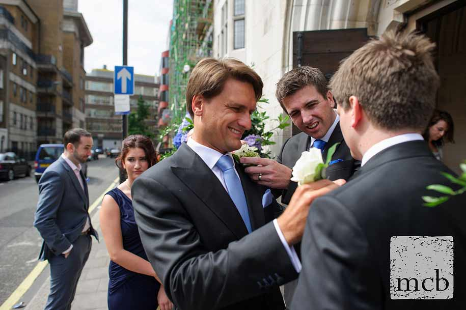 The groom fits an usher's flowers as his brother fixes his