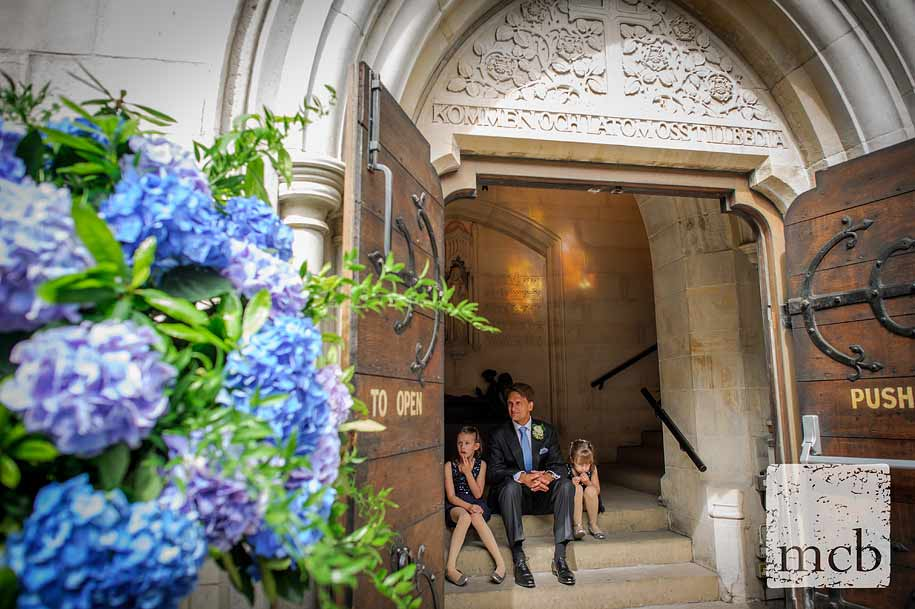 Groom sat on the church steps with the flowergirls