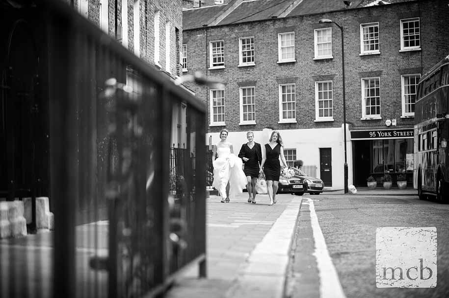 Bride walks towards the church with her bridesmaids