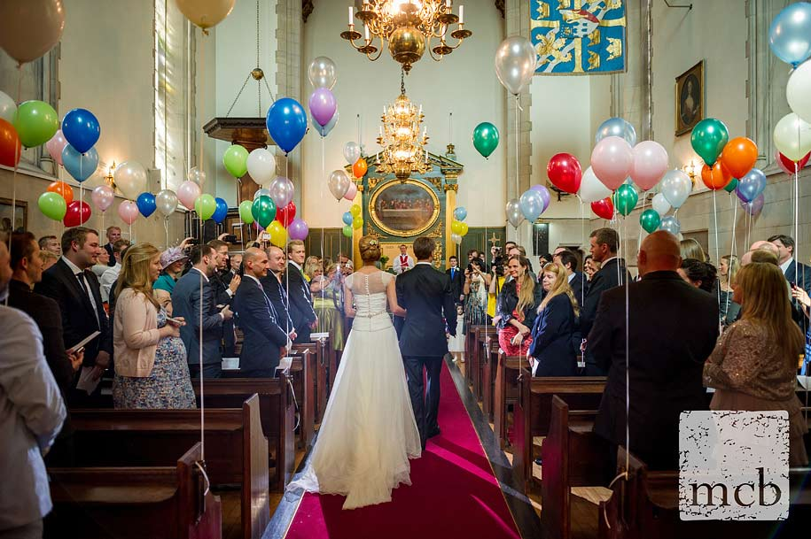 Bride and groom walk down a balloon bedecked aisle