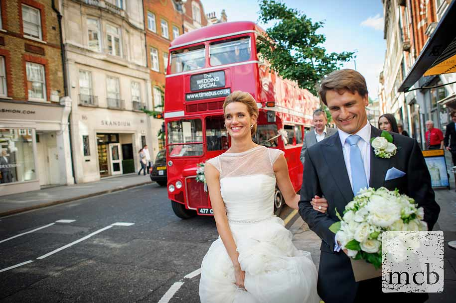 Bride and groom wlak down Marylebone High Street