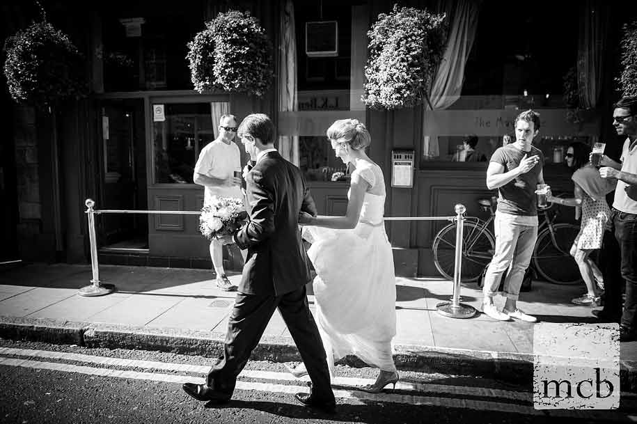 Drinkers watch the bride and groom walk towards the pub