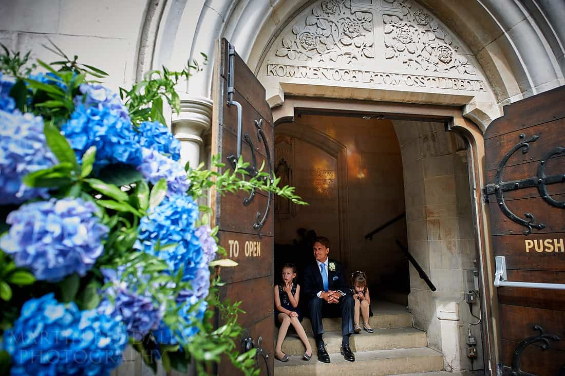 Groom waits on the steps of the Swedish church in London