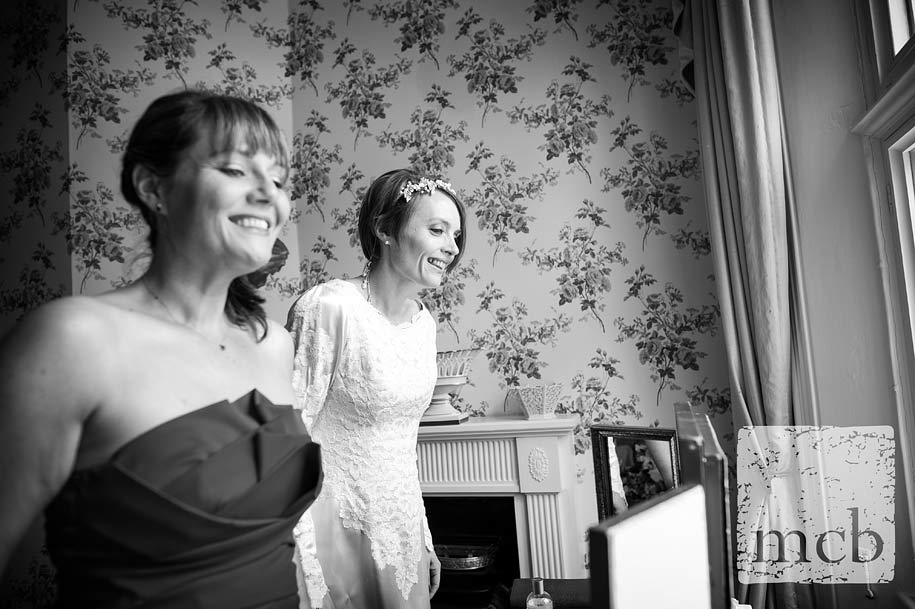 Smiling bride and her sister watching guests arrive