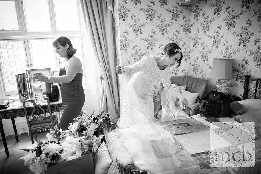 Bride lays out her vintage wedding veil on her bed