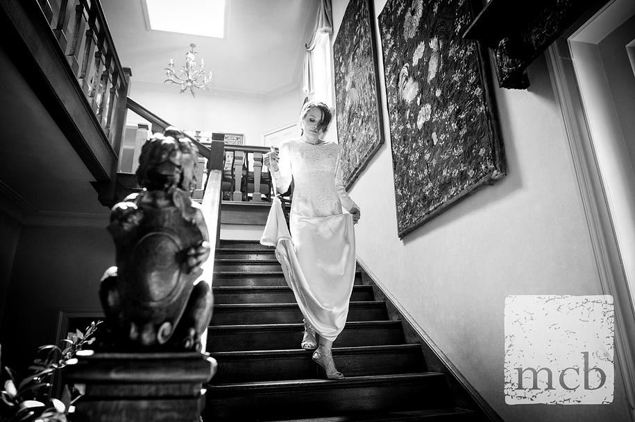 Bride walks down the staircase at wadhurst castle