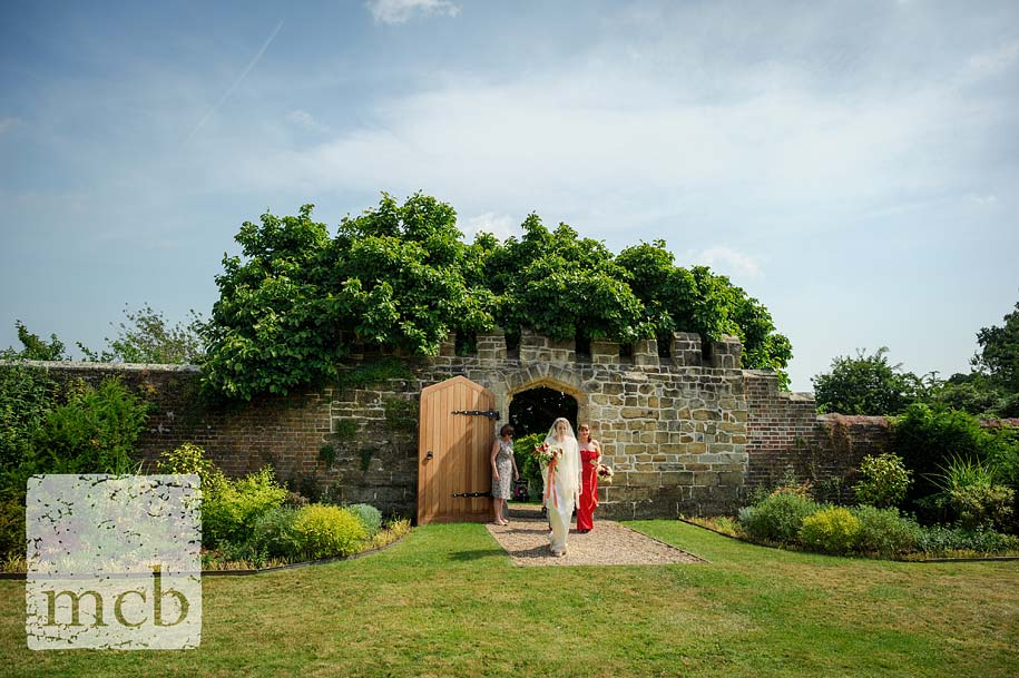 Bride enters the walled garden at wadhurst castle