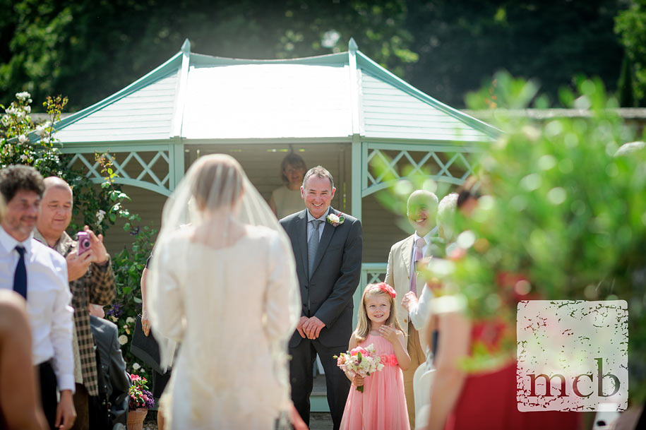 Brdie walks down the aisle in the walled garden
