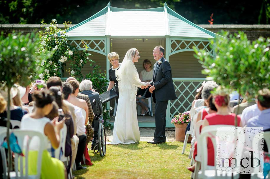 Bride and groom laughing at open air wedding ceremony