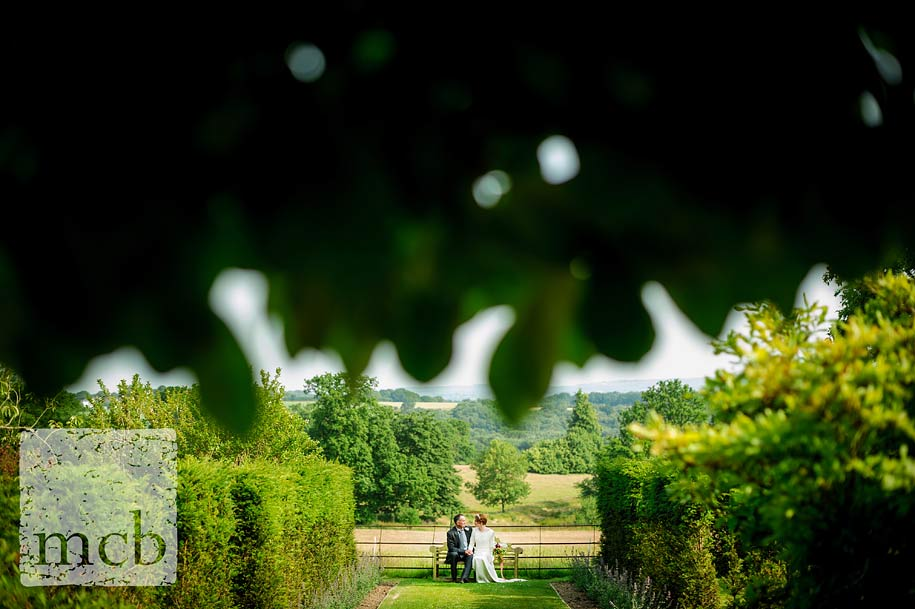 Bride and groom sat in the gardens at Wadhurst Castle