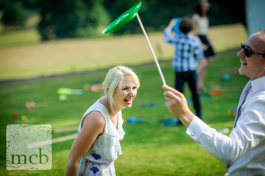 young couple try out plate spinning at a summer wedding