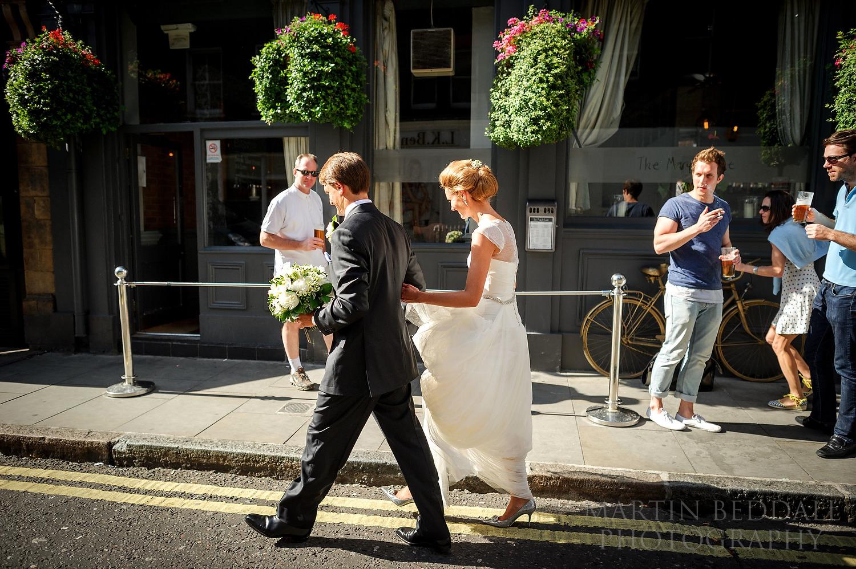 London wedding bride and groom walk past pub drinkers