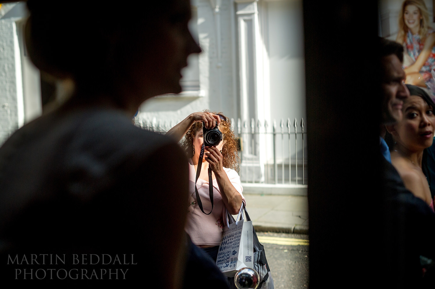 Passerby photographing the bride
