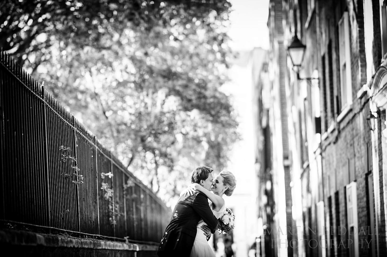 Bride and groom kiss portrait in London street