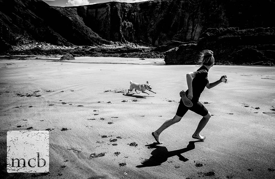 Girls runs with her dog on a Cornish beach